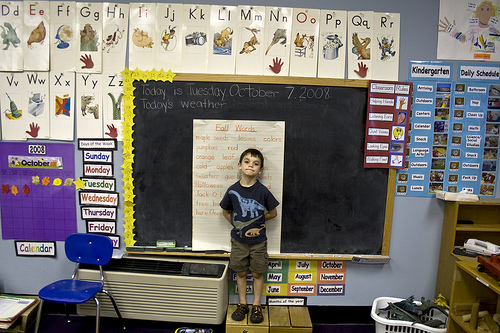 A boy in school, standing in front of a blackboard.