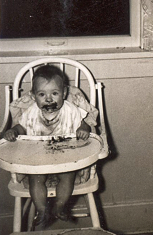 A messy baby from the late 1940s, in her high chair.