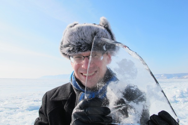 UNI Geography Professor Andrey Petrov, in furry hat and gloves, holds a piece of Lake Baikal ice in front of his face  during his most recent Siberian visit.
