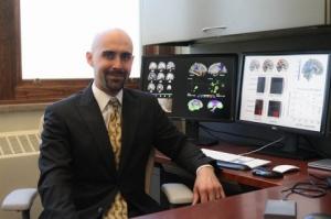 Iowa State University researcher Auriel Willette at computer screens showing brain scans. ISU photo by Blake Lanser.