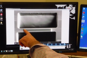 """Kramer points to areas of a sample that have been """"machined"""" with the FIB's gallium ion beam. The bean has hollowed out sections of the sample, leaving a thin strip to be removed for further study. The scale indicates the strip is only about 20 millionths of a meter long."""