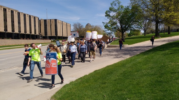 The leading edge of the March for Science Iowa coming down Grand Avenue, with organizer Shamus Roeder wielding the bullhorn.