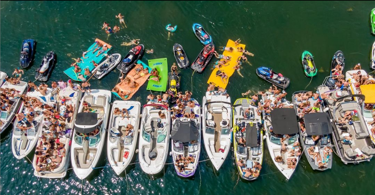 Boats tied together in a row with swimmers and floating air mattresses at one of the Iowa Great Lakes.